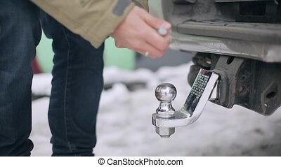 Man putting and fixing new metallic tow hitch to car on...
