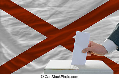 man putting ballot in a box during elections  in front of flag american state of alabama