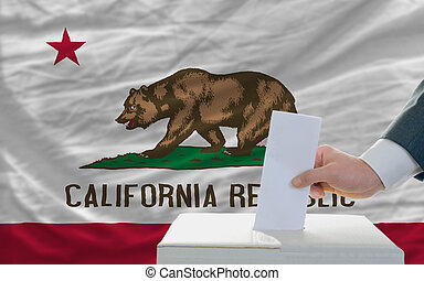 man putting ballot in a box during elections  in front of flag american state of california