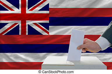 man putting ballot in a box during elections  in front of flag american state of hawaii