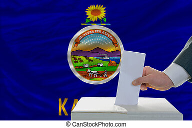 man putting ballot in a box during elections  in front of flag american state of kansas