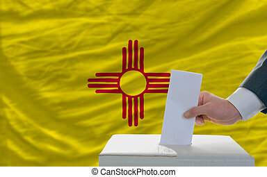 man putting ballot in a box during elections  in front of flag american state of new mexico