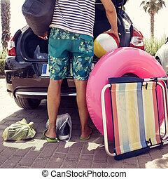 man putting beach stuff in the car