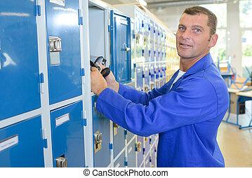 Man putting belongings in a locker
