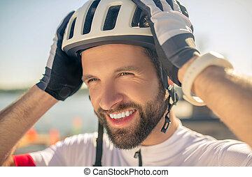Man putting bicycle helmet on his head