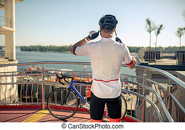 Man putting bicycle helmet standing with his back