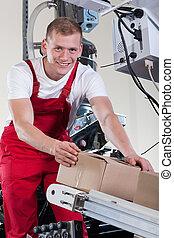 Man putting boxes on automatic conveyor belt