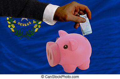 Man putting euro into piggy rich bank and flag of us state of nevada in foreign currency because of insecurity and inflation