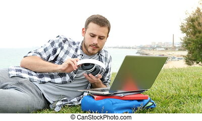 Man putting headphones and e-learning with laptop - Happy...