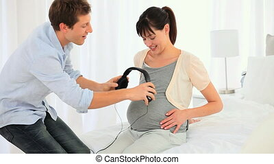 Man putting headphones on the belly of his pregnant wife