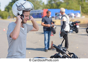 man putting helmet on his student