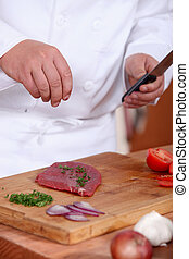 Man putting herbs on a piece of meat