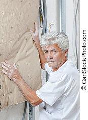 man putting insulation