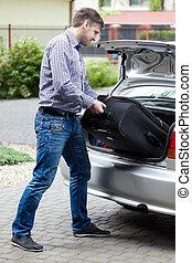 Man putting luggage into car trunk
