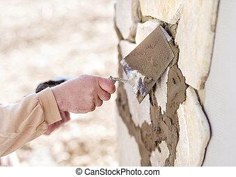 Man putting natural stones on a wall - Mason putting ...