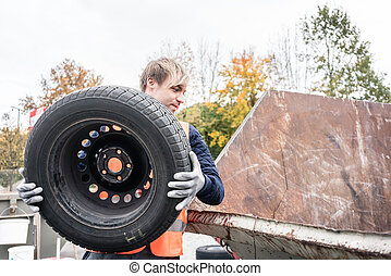 Man putting old tire in container of recycling center - Man...