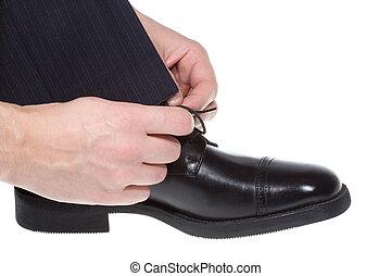 man putting on black shoe