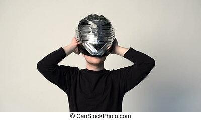 Man putting on performance metal helmet, gesturing thumb up