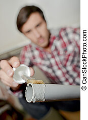 Man putting plastic glue on end of pvc pipe