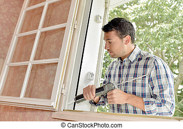 Man putting sealant around window frame