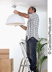 Man putting up a ceiling light