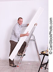 Man putting up coving using a stepladder