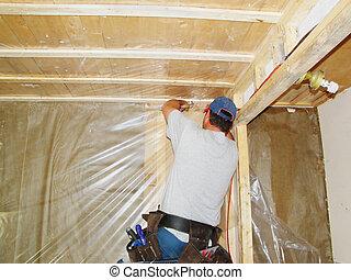 Man putting vapor barrier in house - Construction concept:...