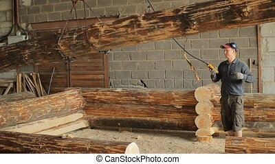 Man raises a wooden beam on the crane in a hangar. Work makes a wooden cottage