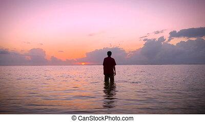 Man raises his arms to a worship pose in a calm ocean to a morning surise