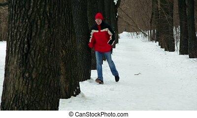 Man random snake runs among trees on park alley at winter day