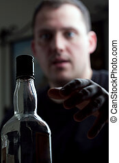 Man Reaching For the Liquor Bottle - A man struggling with...