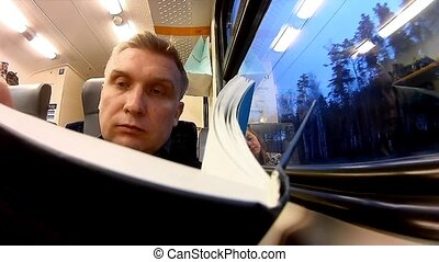 Man read book in a passenger train