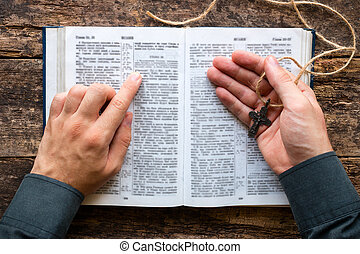 man reading a bible and holding a cross