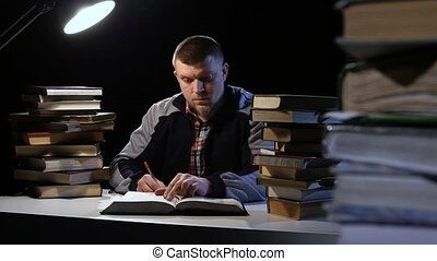 Man reading a book and writes in a notebook. Black background