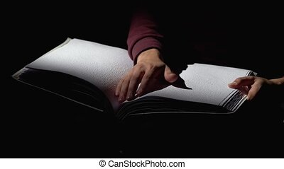 Man reading a book for the blind in a dark room . Close up -...