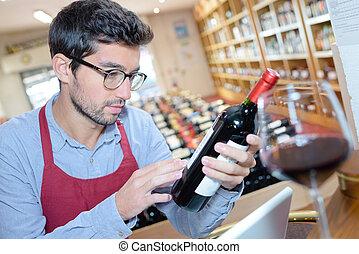man reading a bottle of wine label in wine shop