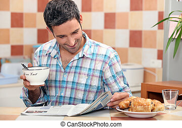 Man reading a magazine at the breakfast table