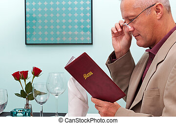 Man reading a menu in a restaurant - Photo of a man reading ...