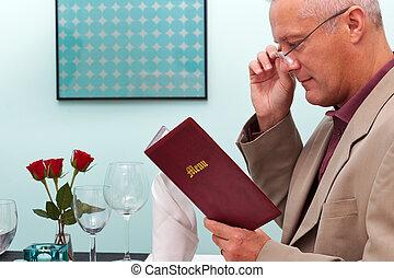 Man reading a menu in a restaurant