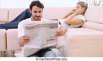 Man reading a newspaper and his girlfriend listens to music