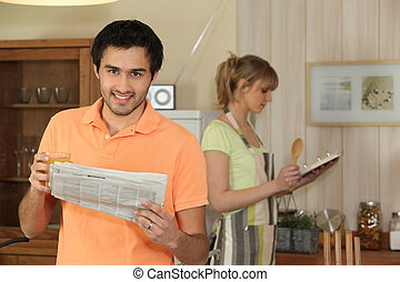 Man reading a newspaper in his kitchen