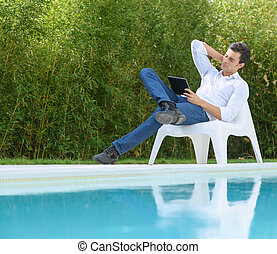Man reading a tablet by the pool