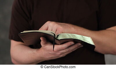 Man Reading Bible - Close up of man's hands and arms as he...