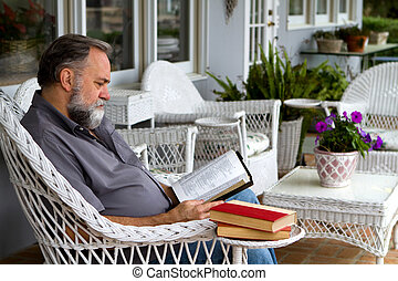 Mature man reads his bible while sitting in a white wicker chair on a porch.