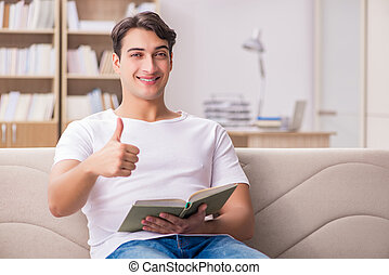 Man reading book sitting in couch sofa