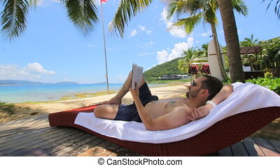 Man reading book under coconut palm tree on Tropical beach