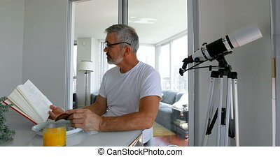 Man reading book while eating breakfast on table 4k