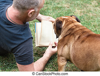 man reading book with a dog on the grass