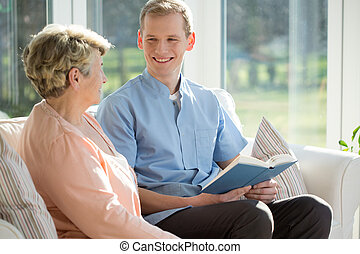 Man reading book with elderly woman