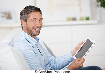 Man Reading Ebook While Sitting On Sofa